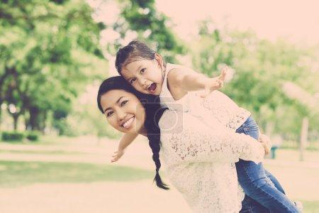 Foto de Feliz madre piggybacking su hijita juguetón - Imagen libre de derechos