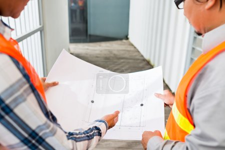 Construction workers discussing house plan