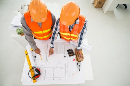 Photo for Construction workers discussing plan of the building in office - Royalty Free Image