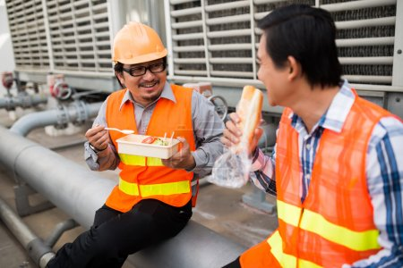 Photo for Two Asian plant engineers sitting on the pipe, eating lunch and talking - Royalty Free Image