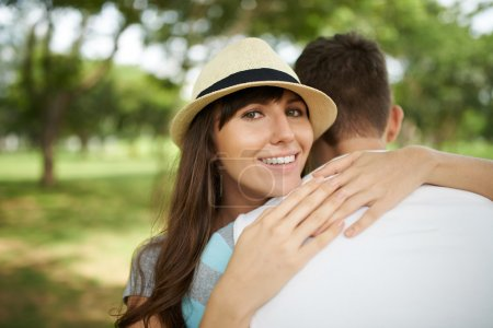 Photo for Portrait of happy woman embracing her boyfriend and looking at the camera - Royalty Free Image