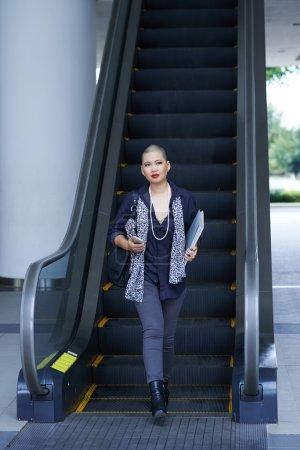 Photo pour Directrice artistique féminine descendant l'escalier roulant - image libre de droit