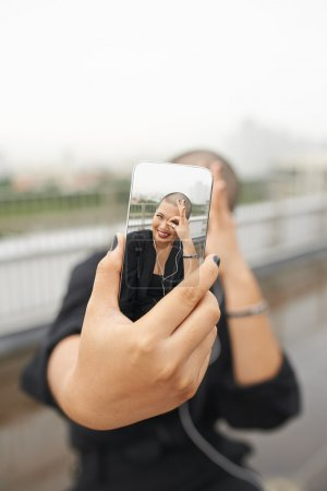 Photo for Young extravagant woman taking selfie with her modern smartphone - Royalty Free Image
