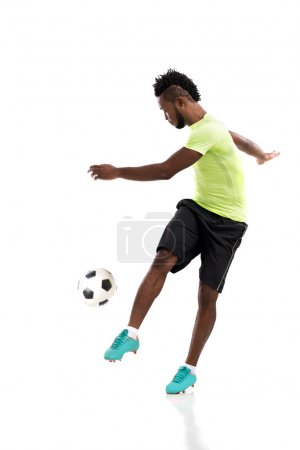 Professional player kicking soccer ball