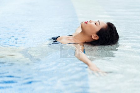 Asian woman relaxing in the pool