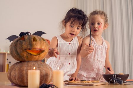 Two girls making Halloween decorations