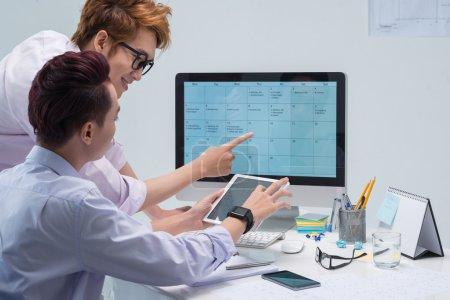 colleagues filling business calendar
