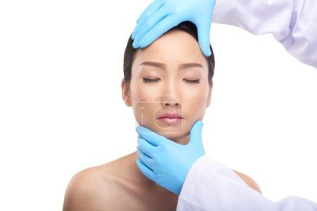 Doctor examining facial skin of woman