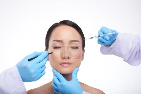 Preparing woman for facial plastic surgery