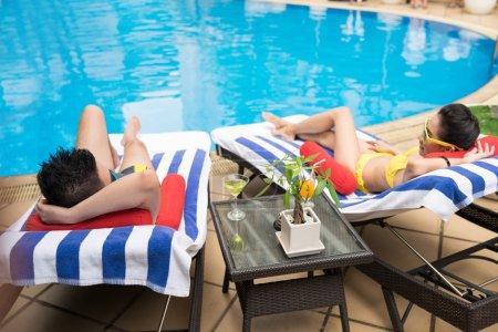 Photo pour Couple allongé sur les transats devant la piscine - image libre de droit