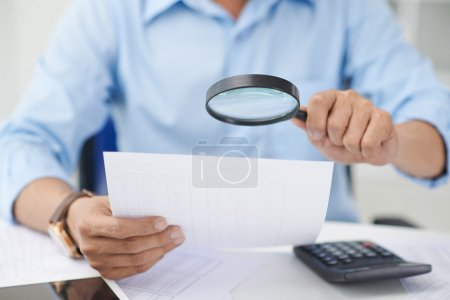 Photo pour Conseiller financier à la recherche de chiffres avec loupe - image libre de droit