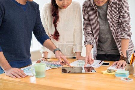 Photo pour Trois designers examine le plan de la conception sur le touchpad - image libre de droit