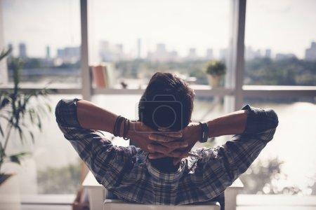 Photo pour Homme se détendre dans son fauteuil et profiter de la vue depuis la fenêtre de bureau - image libre de droit