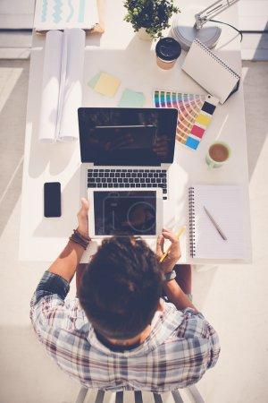 Designer using digital tablet and laptop