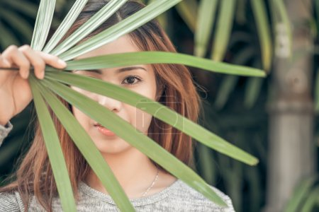 Photo for Portrait of beautiful Vietnamese woman holding palm leaves in front of her face - Royalty Free Image