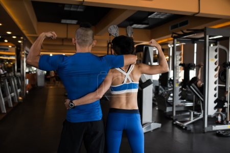Fit couple hugging and showing biceps