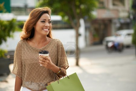 Happy beautiful Asian woman with purchases