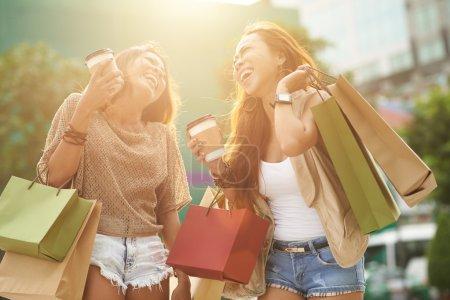 Photo pour Jolies jeunes femmes avec des sacs à provisions s'amuser ensemble - image libre de droit