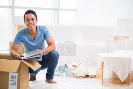 Photo for Cheerful Vietnamese man getting his belongings out of the cardboard box - Royalty Free Image