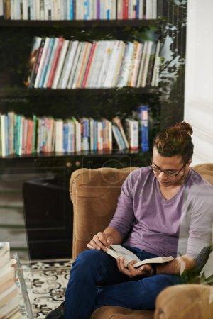 Photo pour Jeune homme lisant un livre absorbant dans une bibliothèque - image libre de droit