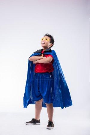 Foto de Valiente chico confiado en traje de superhéroe mirando hacia arriba - Imagen libre de derechos