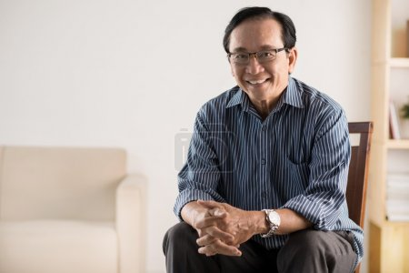 Photo pour Vieil homme asiatique assis sur une chaise et souriant à la caméra - image libre de droit