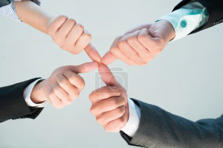 Hands of business people connecting thumbs