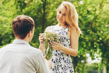 Young man giving bouquet to girlfriend