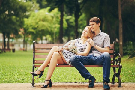 Happy young couple resting in park