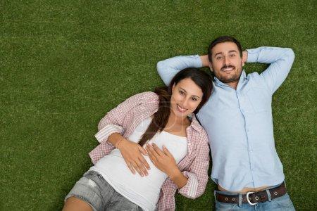 Photo pour Couple souriant couché sur l'herbe verte, vue d'en haut - image libre de droit