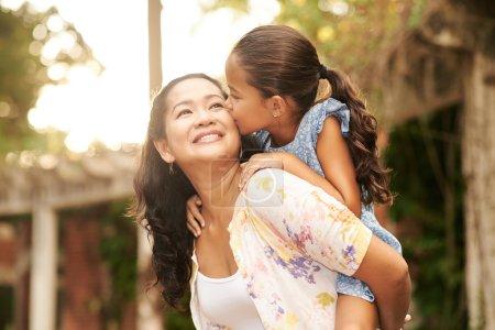 Photo pour Femme donnant le tour de piggyback à sa fille à l'extérieur - image libre de droit