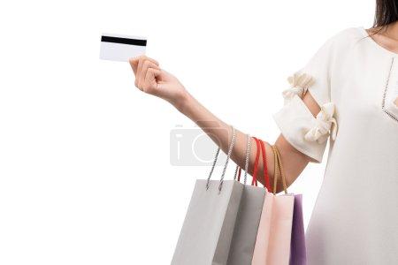 Photo pour Main de femme accro au shopping avec carte de crédit et sacs à provisions - image libre de droit
