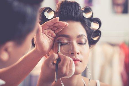 Photo pour Styliste masculin créant un maquillage parfait pour les yeux smokey - image libre de droit