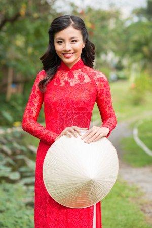 Photo pour Portrait de jolie fille vietnamienne en robe traditionnelle tenant un chapeau conique - image libre de droit