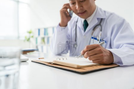 Doctor talking and making notes