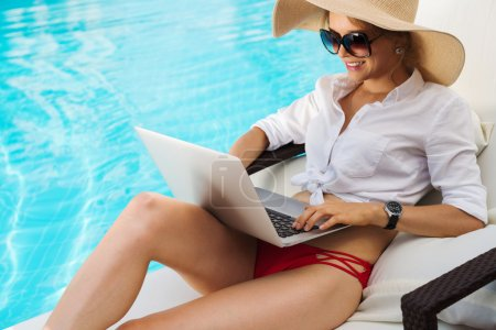 Photo for Beautiful smiling woman in sunglasses sitting in chaise-longue with a laptop - Royalty Free Image