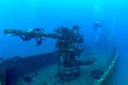 Divers exploring the ship wreck in tropical sea