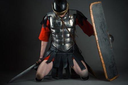 Photo pour Soldat fatigué agenouillé avec un bouclier et une épée dans les mains isolées sur fond gris - image libre de droit