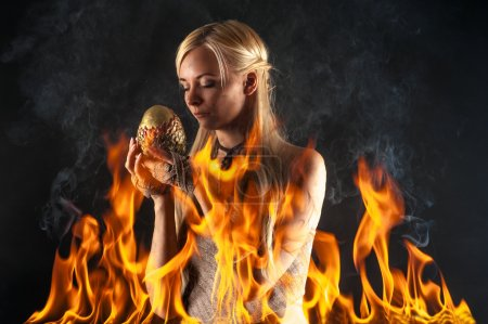 attractive woman with a dragon egg in the fire