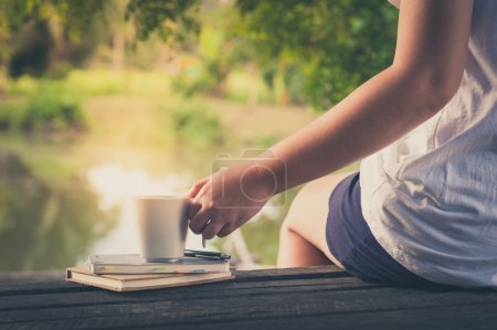 Photo for Woman left hand holding coffee cup beside notebooks on rustic wood bench with rural lake view in background in morning time on weekend with vintage filter effect - Royalty Free Image