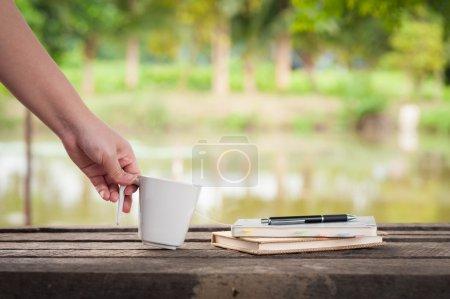 Photo pour Femme main gauche tenant tasse de café à côté des cahiers sur banc en bois rustique avec vue sur le lac rural en arrière-plan flou le week-end avec scène du matin - image libre de droit