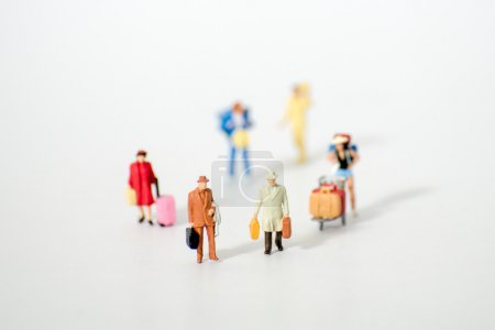 Miniature traveler figures with luggages waiting for departure at Airport