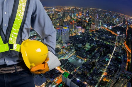 Photo for Engineer holding a yellow helmet for safety of the workers. A modern high-rise structures in the background. - Royalty Free Image