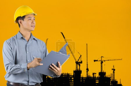 Photo pour Ingénieur asiatique surveiller le projet de construction avec une grande grue en arrière-plan . - image libre de droit
