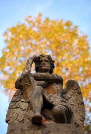 The thinker statue of an angel with a book in autumn