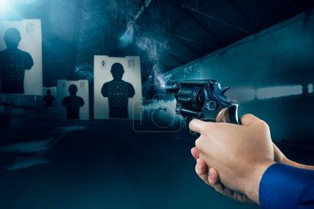 Photo pour Agent de police tenant une arme à feu à un champ de tir - image libre de droit