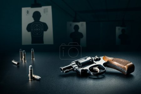 Gun on a table with bullet shells