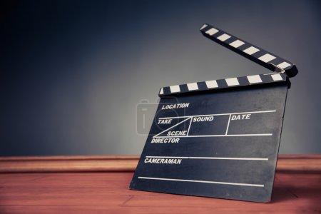 Photo pour Movie clapper avec éclairage dramatique. Objet industrie cinématographique sur fond gris - image libre de droit