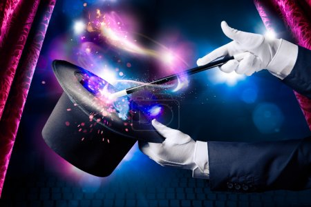 Photo pour Image à contraste élevé de mains magiciennes tient baguette magique et chapeau - image libre de droit