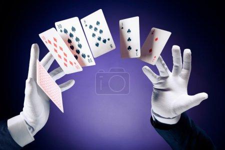Photo pour Image à contraste élevé de mains magiciennes faisant des tours de cartes - image libre de droit